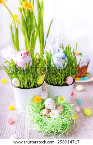 Easter decoration with green grass,flowers,eggs,cake and birds - stock photo
