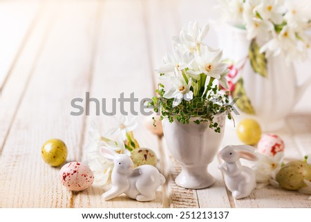 Easter decoration with spring flowers,chocolate eggs and rabbits - stock photo