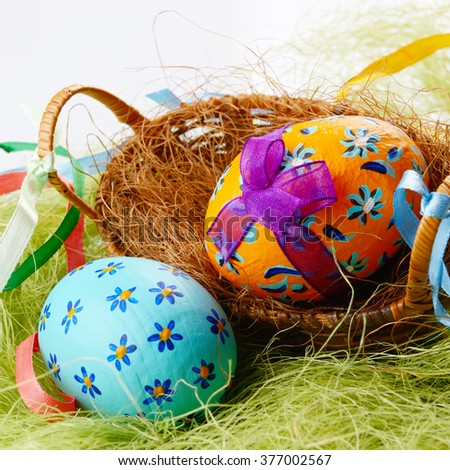 Easter decorations - eggs, cake and basket on the tabletop - stock photo