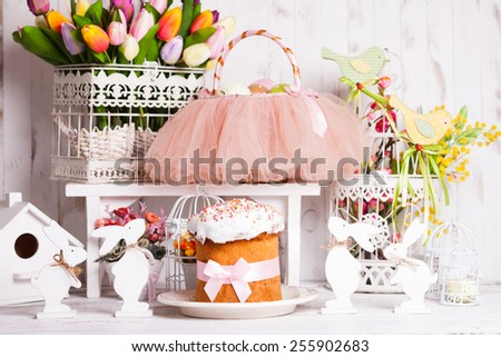 Easter decorations - spring flowers, rabbits, cake and tutu basket - stock photo