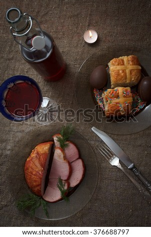 Easter dinner served on burlap tablecloth. Meat, hot cross buns, chocolate eggs and wine, top view - stock photo