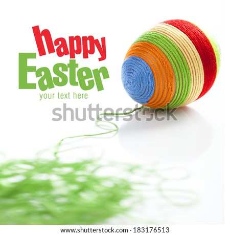 Easter egg covered with various colors wool. Bunch of green wool on first plan. Space for text - stock photo