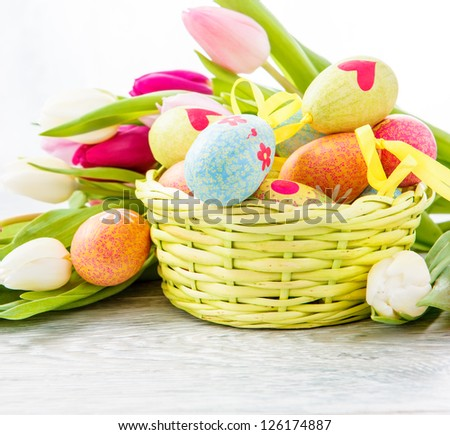 Easter egg decoration in basket and tulip flowers - stock photo