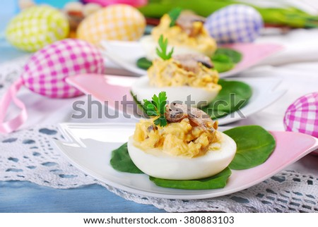 easter egg halfs stuffed with fried mushrooms,cheese and mayonnaise on spinach leaves - stock photo