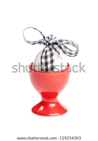 Easter egg with checked ribbon is in red egg cup, isolated on white. Traditional symbol of the feast - stock photo