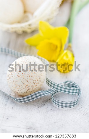 Easter egg with daffodils on white wooden background - stock photo