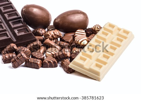 Easter eggs and assorted chocolate on white background - stock photo