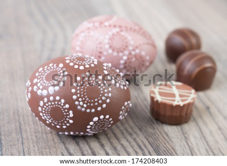 Easter eggs and chocolate pralines on wooden table - stock photo