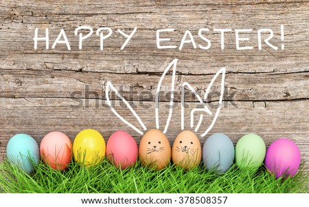 Easter eggs and cute bunny in green grass. Festive decoration. Happy Easter! - stock photo