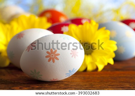 Easter eggs and daisy flowers on wooden table - stock photo