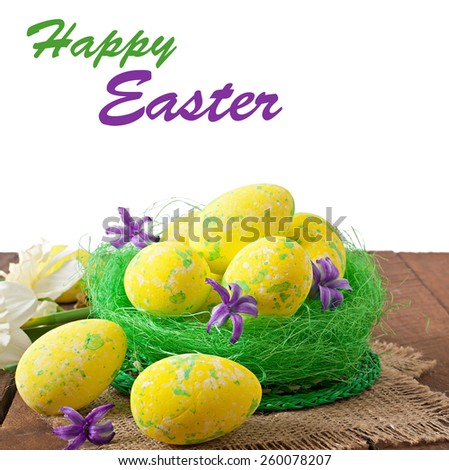 Easter eggs and flowers on wooden background - stock photo