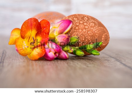 Easter eggs and freesia flowers on wooden table, text space, shallow DOF, focus on the front egg  - stock photo