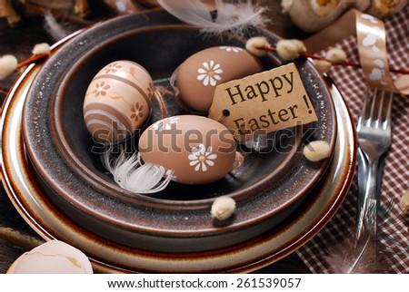 easter eggs and paper tag with greeting text in plate on rustic wooden table - stock photo