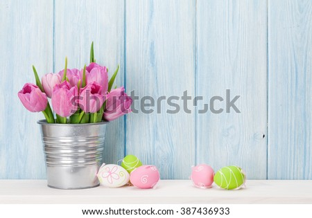 Easter eggs and tulips bouquet on shelf in front of wooden wall. View with copy space - stock photo