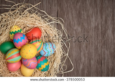 Easter eggs background. Hand painted multicolored decorated eggs on straw nest, wood, copyspace. Unusual creative holiday greeting card  - stock photo