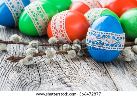 Easter eggs decorated with lace and willow branch on wooden background. Selective focus, copy space - stock photo