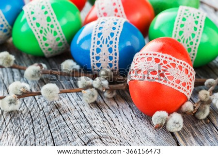 Easter eggs decorated with lace on wooden background. Selective focus - stock photo