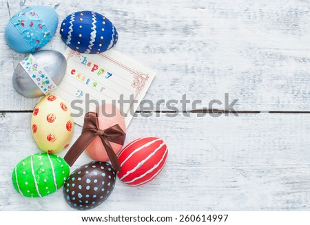 easter eggs decorated with ribbon and card on wooden background - stock photo