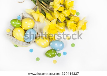 Easter eggs decorated with yellow daffodil flowers - stock photo