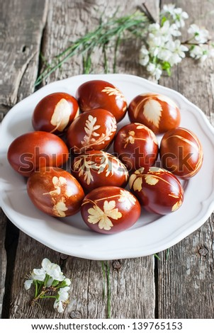 Easter Eggs Decoration with fresh plants on a white plate - stock photo