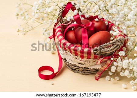 Easter eggs in a basket with red checkered napkin and white flowers (horizontal shot) - stock photo