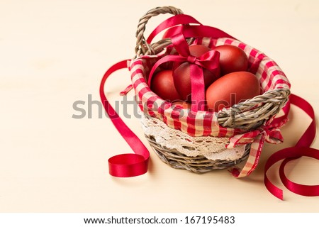Easter eggs in a basket with red checkered napkin on beige table  - stock photo