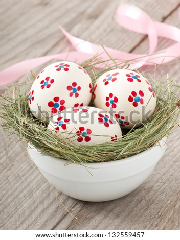 Easter eggs in a bowl decorated with a nest on the wooden table - stock photo