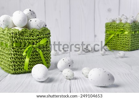 Easter eggs in a green basket on a white table - stock photo