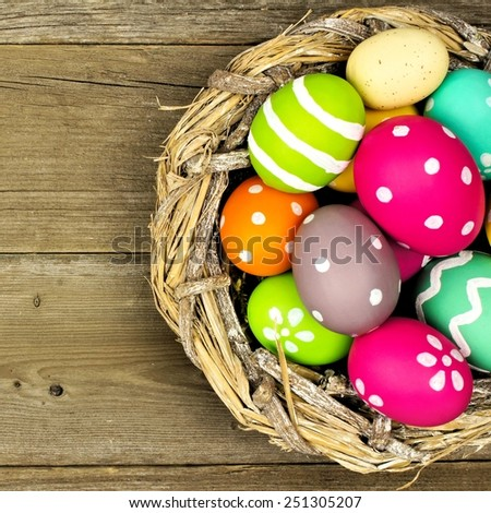 Easter eggs in a nest close up over an old wood background - stock photo