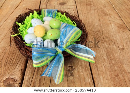Easter eggs in a nest on a wooden table.  - stock photo