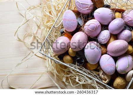 Easter eggs in a white wire basket on a wooden table - stock photo