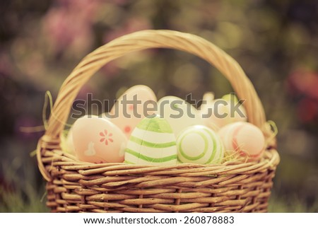 Easter eggs in basket against blurred green background. Spring holidays concept - stock photo
