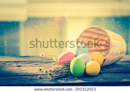 Easter eggs in basket  on color wooden background - stock photo