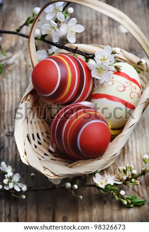 Easter eggs in basket on wooden background - stock photo