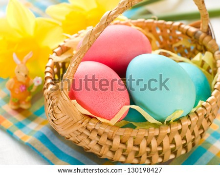Easter eggs in basket with daffodil, selective focus - stock photo