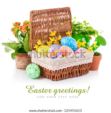 easter eggs in basket with spring flowers and green leaves isolated on white background - stock photo