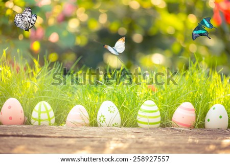 Easter eggs in grass against blurred green background. Spring holidays concept - stock photo