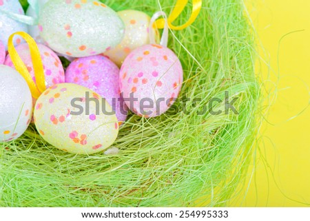 Easter eggs in green nest over yellow paper - stock photo