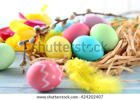 Easter eggs in nest on a blue wooden table - stock photo