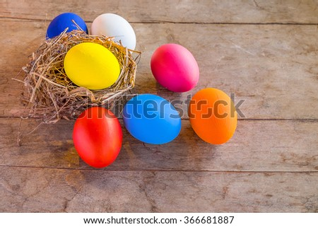 Easter eggs in nest on rustic wooden planks.Soft focus,Low light.(selective focus) - stock photo
