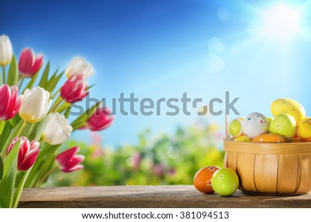 Easter eggs in the basket on wooden boards - stock photo