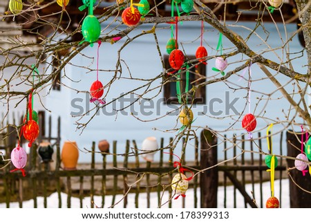 Easter eggs on a tree in front of wooden cottage. Slovakia. - stock photo