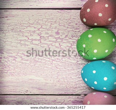 Easter eggs on pink wooden background. Focus on a wooden table. toned image - stock photo