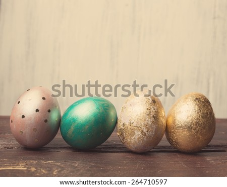 Easter eggs on rustic wooden table. Holiday background. Tinted photo. - stock photo