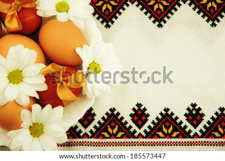 Easter eggs on the embroidered towel - stock photo