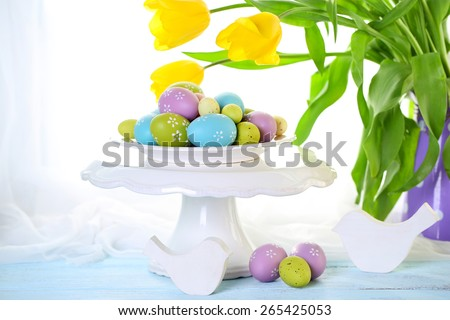 Easter eggs on vase and tulips on table on bright background - stock photo