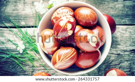 Easter Eggs on Wooden Table Decorated with Natural Fresh Leaves and Boiled in Onions Peels. Top view. Toned  - stock photo