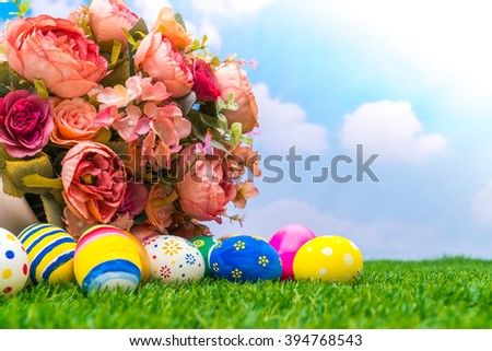 Easter eggs with artificial flower on Fresh Green Grass - stock photo
