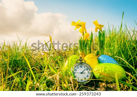 Easter eggs with daffodils and a clock - stock photo