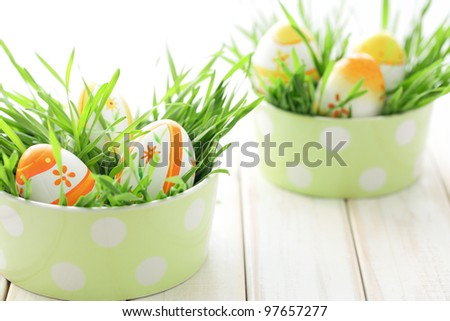 Easter eggs with fresh grass on table. - stock photo